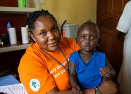 "Midwife Irene Holds The Child Of Former Midwife Student Alice Jaguru Who Helped Deliver.        Nigerian Midwife Irene Ewuzie And Ugandan Midwife Mary Akotimolla Work For United Nations Population Fund (UNFPA) In Kajo Keji, South Sudan, As Part Of The ""Deploying Midwives Project"" That Began In 2013. The Project Is Aimed At Deploying Qualified International Midwives Across South Sudan To Assist In Capacity Building And Strengthening Midwifery Services, Thereby Reducing Maternal Deaths. Irene And Mary Work At The Hospital Providing Hands-on Training To Midwife Students, Helping To Save Lives.   MAF Regularly Flies For UNFPA, Primarily Delivering The Midwives To And From Their Area Of Work. On This Day, 22 October, Pilot Eivind Lindtjorn Drops Off Seven Midwives To Four Locations In Western Equitoria State: Kajo Keji, Nimule, Yei, And Maridi Following A Holiday Break From Work."